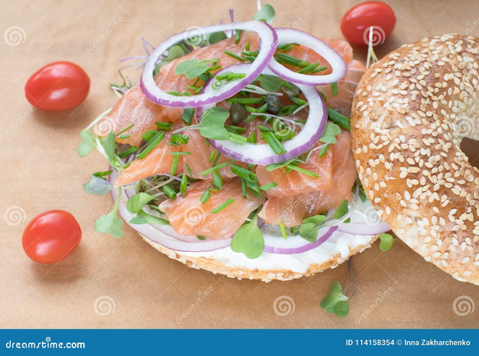 Sanduíche do Bagel com queijo do creame, salmão, cebola, tomate, verdes, ch