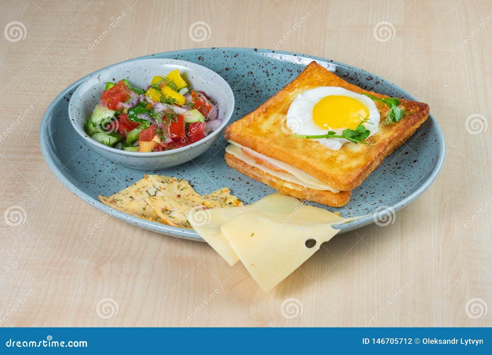 Sanduíche do ovo frito e de presunto, tomate, pepino e salada e queijo da pimenta em uma placa