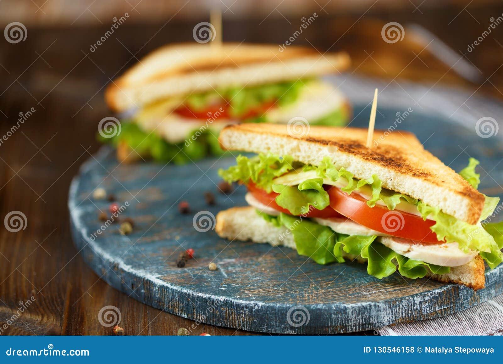Sanduíche dois saboroso com galinha, tomates, alface, queijo em uma placa de madeira em um fundo escuro