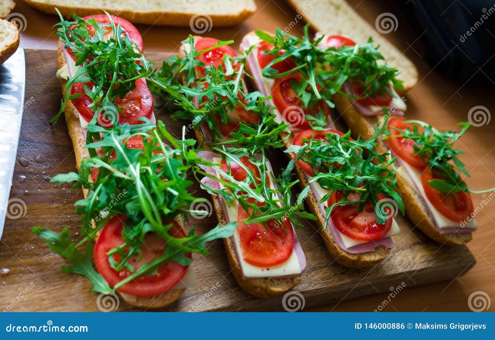 Sanduíche submarino fresco do baguette com presunto, queijo, tomates e o foguete selvagem Foco seletivo