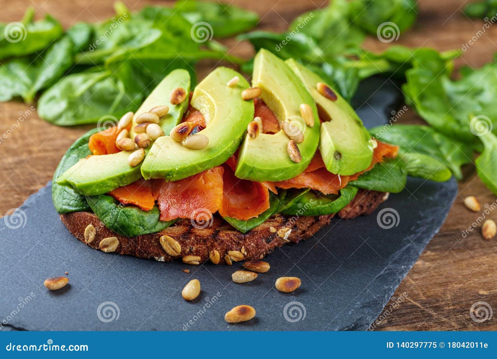 Sanduíche wholegrain do pão dos salmões e do abacate com espinafres