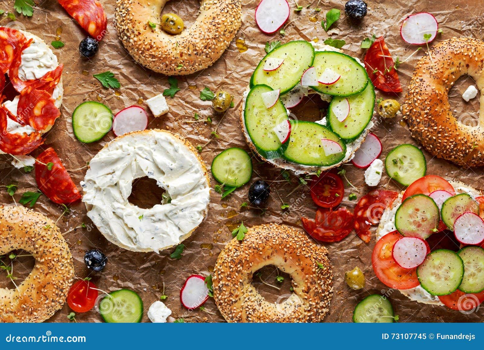 Sanduíches deliciosos do Bagel com queijo macio, chouriço e vegetais