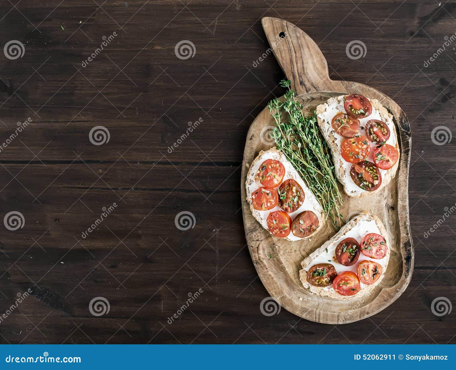 Sanduíches ou brushetta com os tomates de cereja roasted, queijo macio,