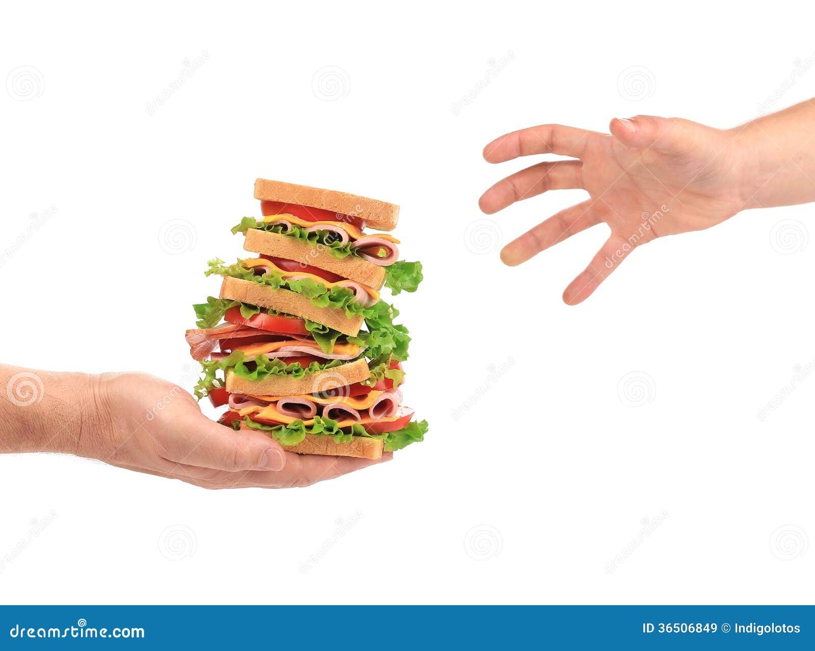 Sandwich avec la tomate et le fromage dans des mains.