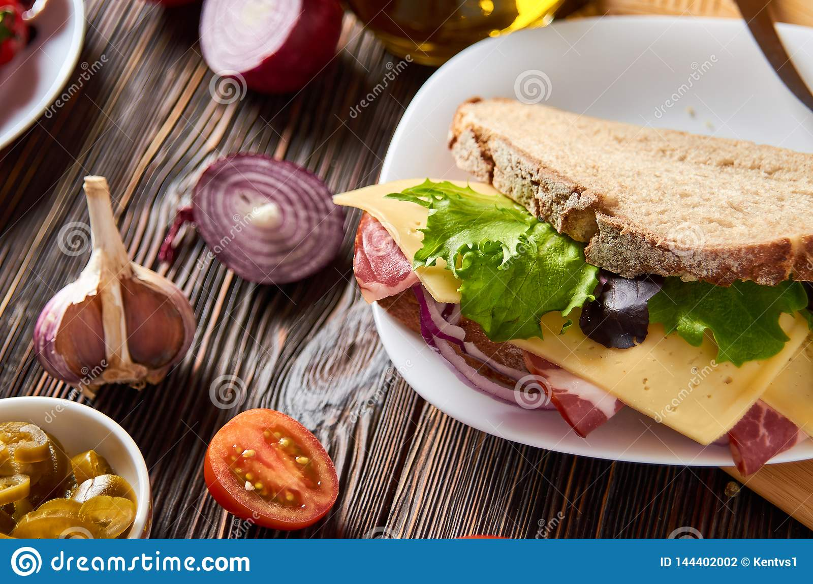 Sandwich with bacon, cheese, garlic, jalapeno pepper and herbs on a plate