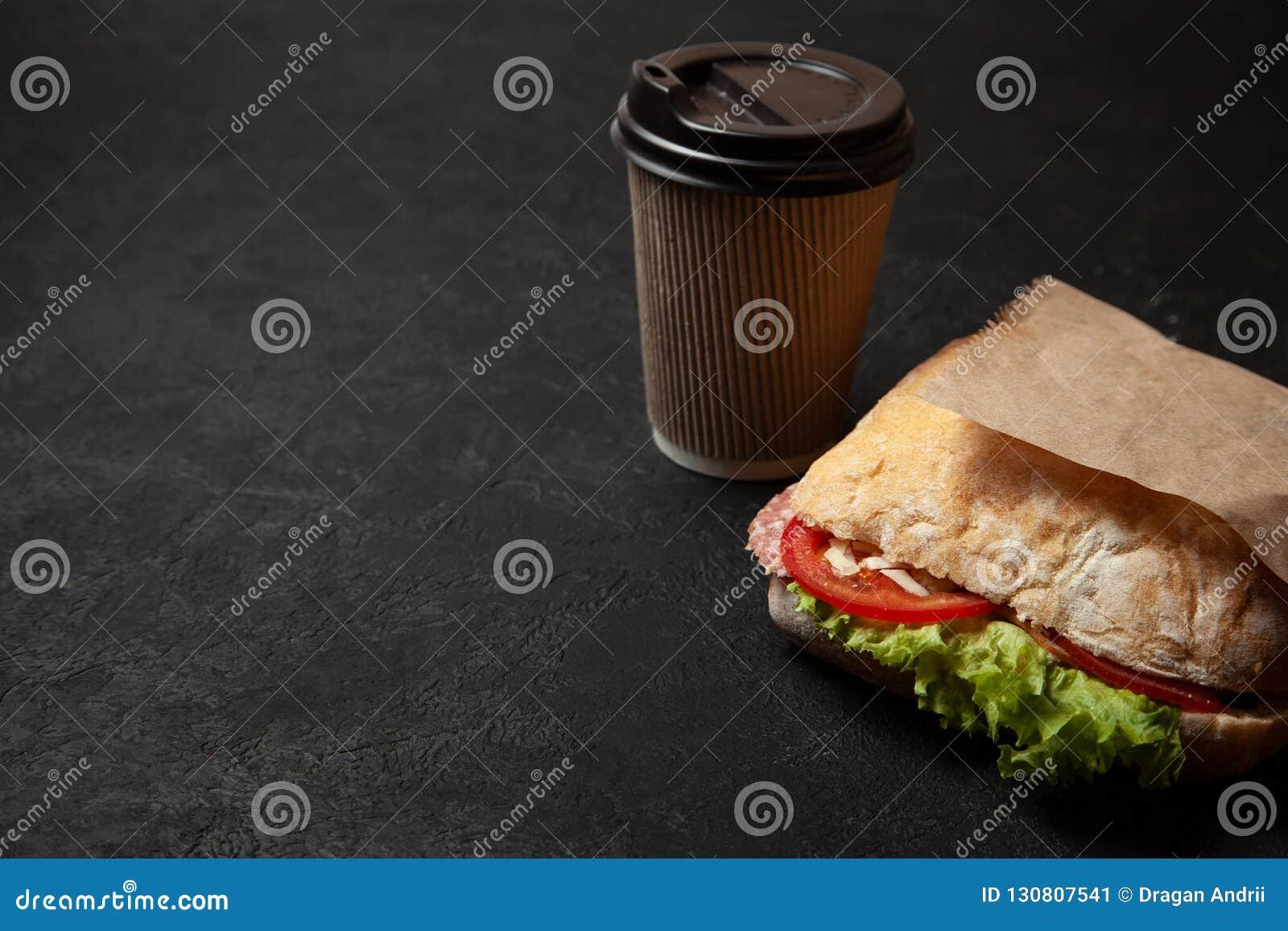 Sandwich en kop van koffie op zwarte achtergrond Ochtendontbijt of snack wanneer hongerig Straatvoedsel om te gaan Exemplaarruimt