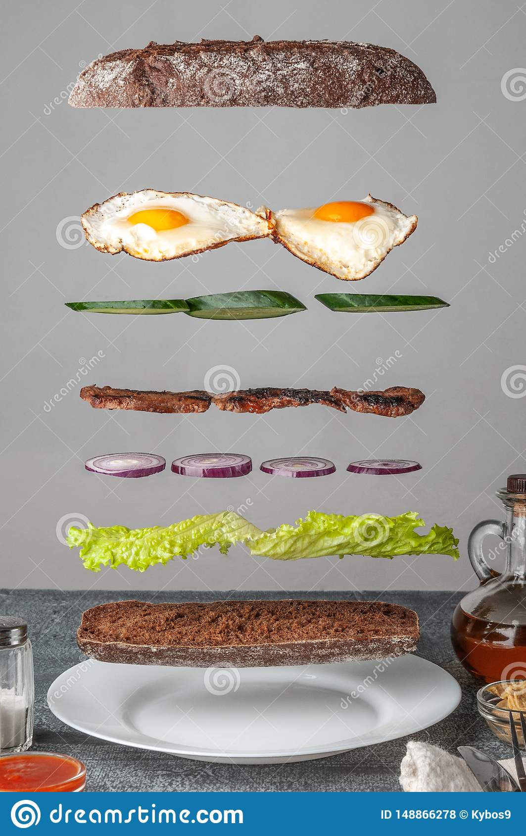 Sandwich ingredients are levitated in the air with crispy baguette, lettuce, cucumber, red onion, grill meat and scrambled eggs.