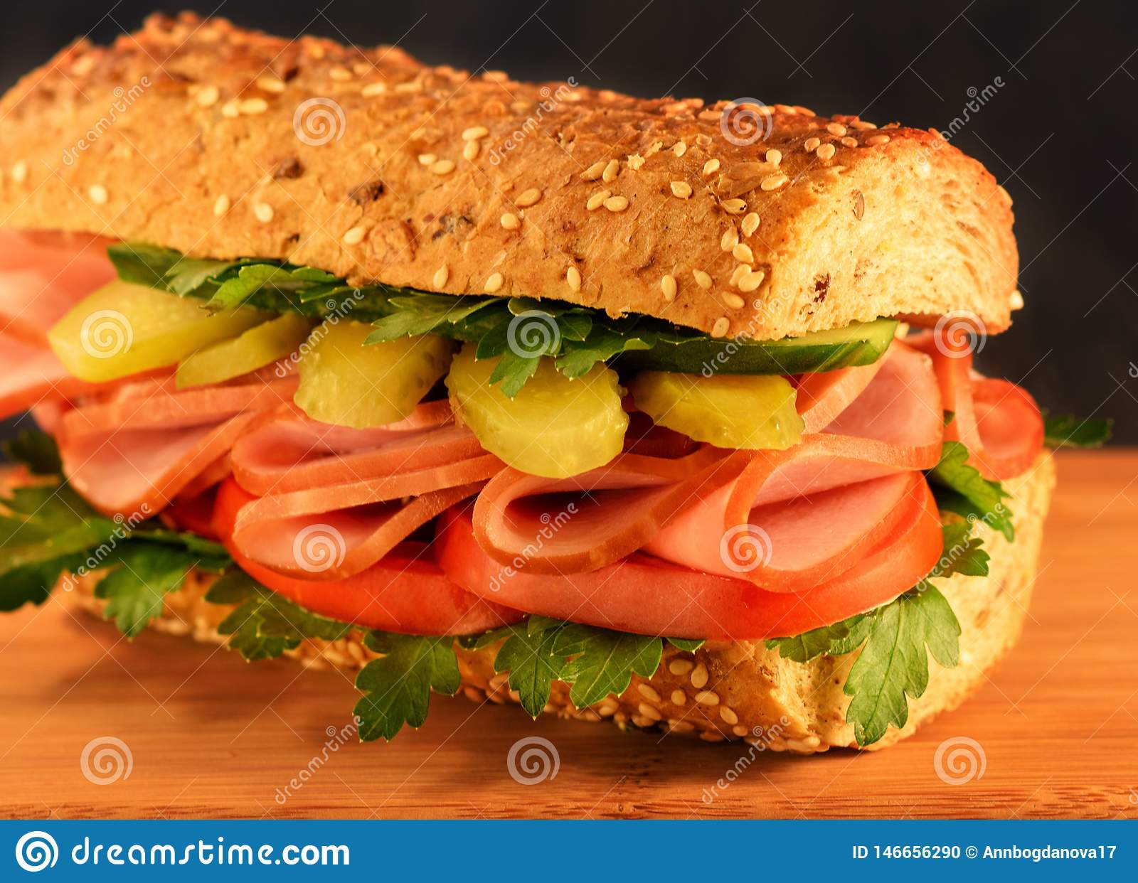 Close-up sandwich  with ham, pickled cucumber, tomato and greens. Sesame Bun