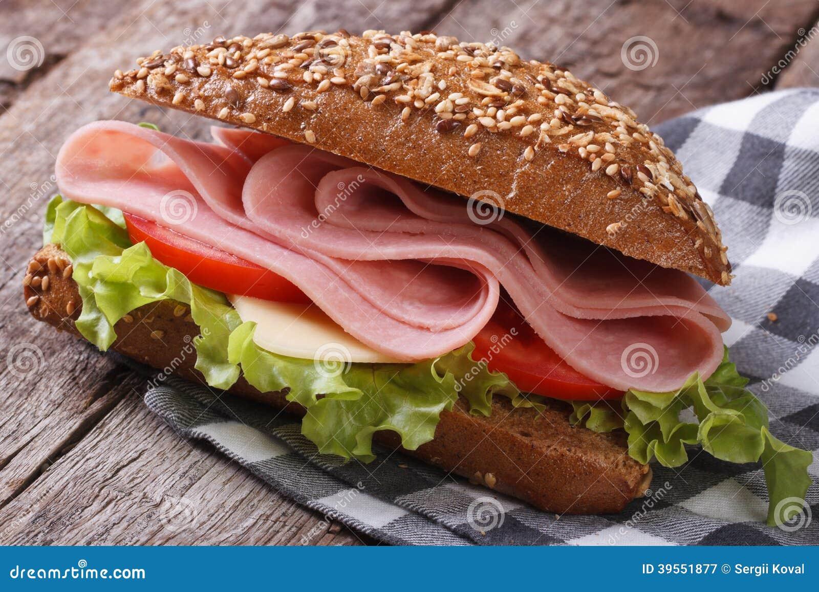 Sandwich mit Schinken, Kopfsalat und Tomaten auf einer alten Tabelle