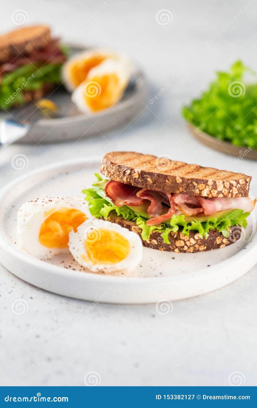 Sandwich mit Speck, Schwarzbrot, Salat auf Platte