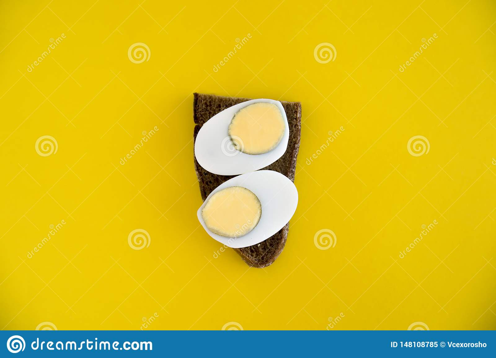 A sandwich of rye bread and boiled egg lies on a yellow background. Breakfast for diet. Toast with bread and egg dietary breakfast