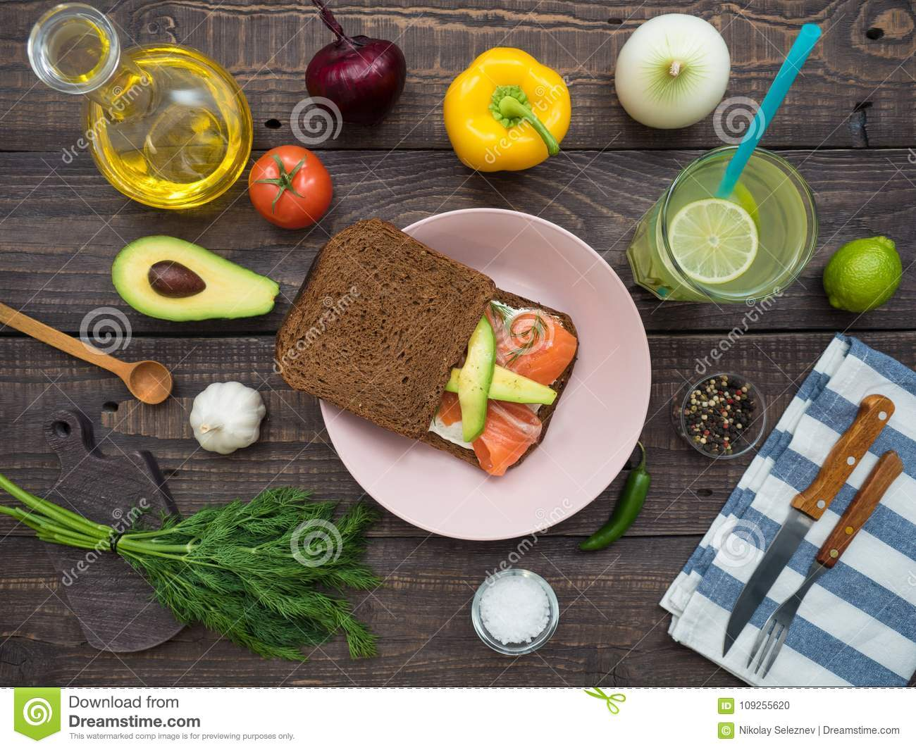 Sandwich with salmon, black bread on a plate, vegetables and a glass of lemonade