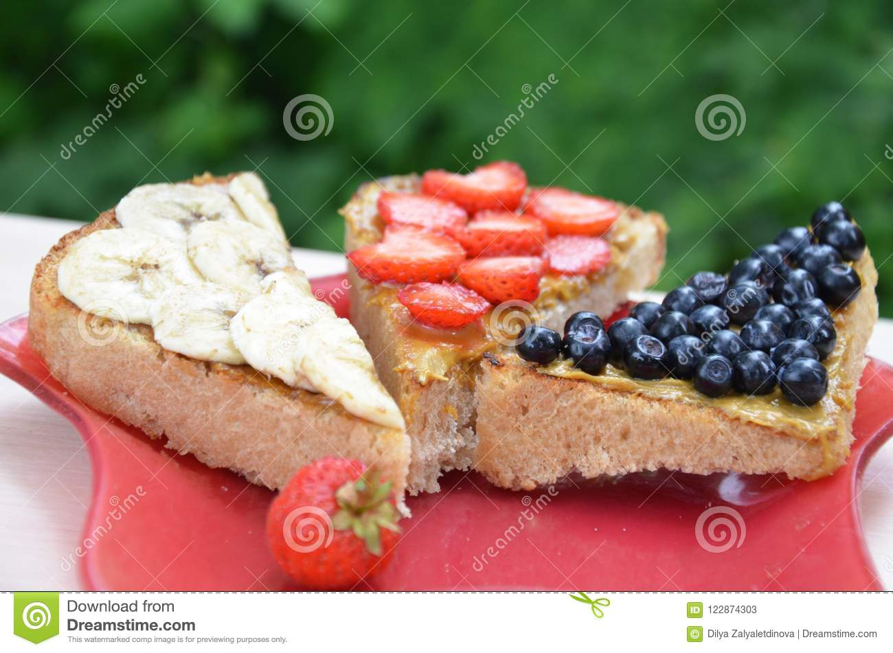 sandwich with strawberry blueberries and peanut butter on a red plate. top view of a sandwich on a background of green foliage in