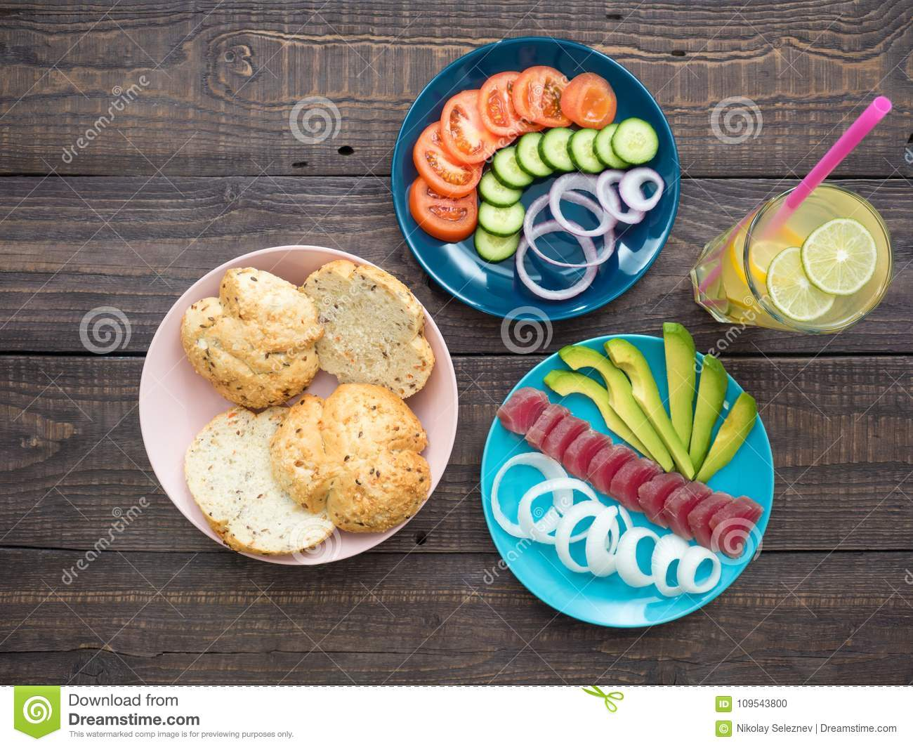 Sandwich with tuna on a plate, vegetables and a glass of lemonade