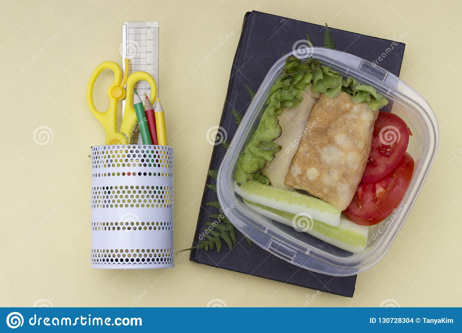 Sandwich with vegetables in a container, school lunch, multicolored pencils and book on a yellow background, top view