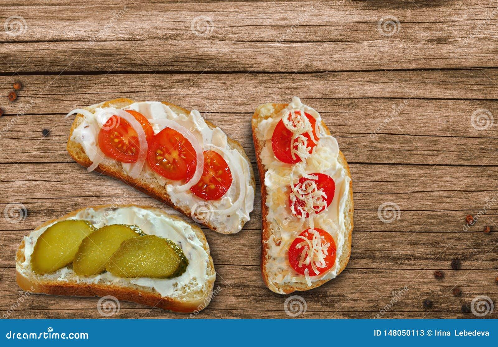 Sandwiche mit Käse, Kirschtomaten und Gurken mit Hüttenkäsepaste auf einem Holztisch