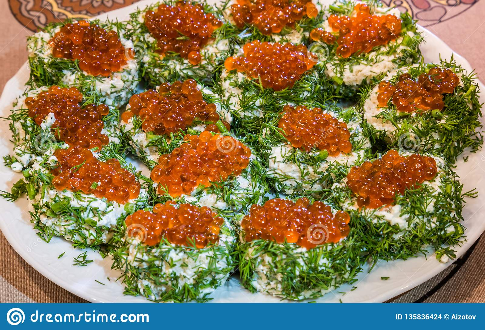 Sandwiches with red caviar and greens on a plate