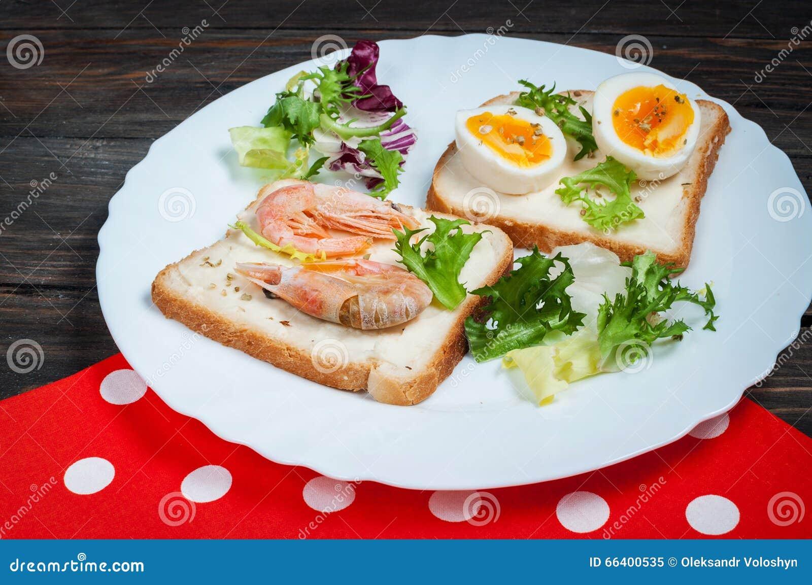 Sandwichs avec la crevette, oeuf, basilic, salade, pain sur le fond en bois Casse-croûte froids délicieux Repas végétariens Conso