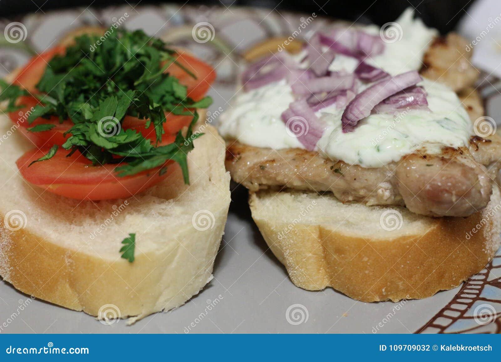 Sandwichs rustiques avec du porc et tomates et tzatziki