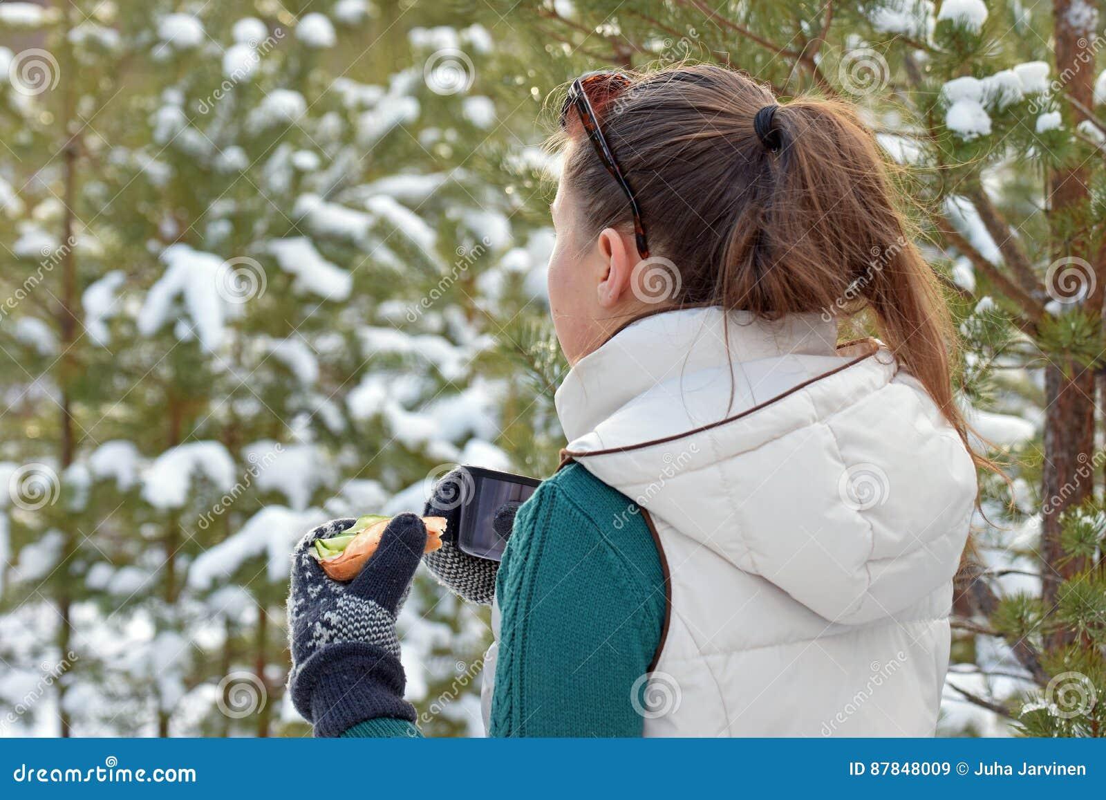 Sandwitch och kaffe för ung kvinna rånar hållande i vinterskog