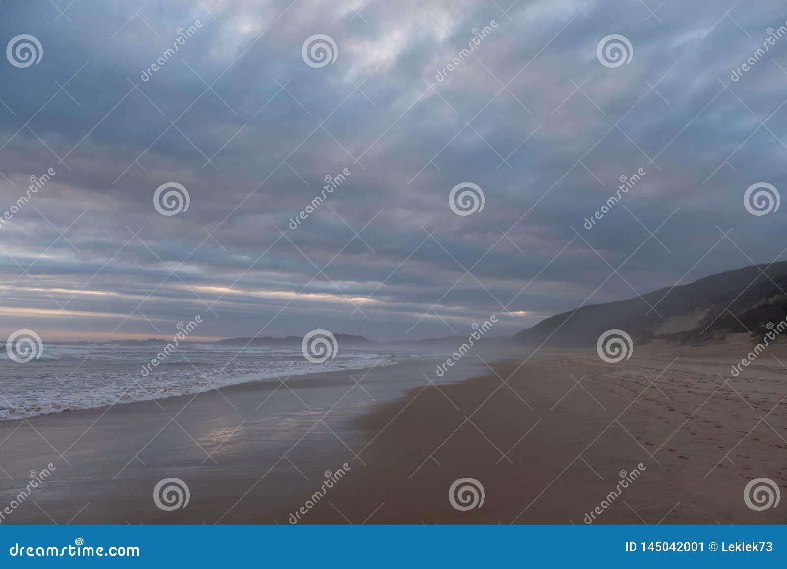 Sandy Beach quieto em Brenton no mar, Knysna, fotografado no pôr do sol, África do Sul