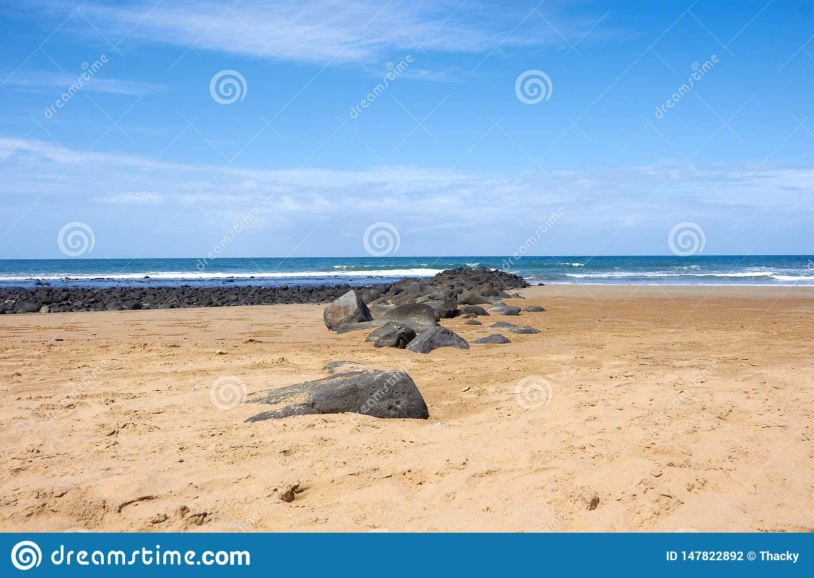 Sandy beach with rocks by the surf