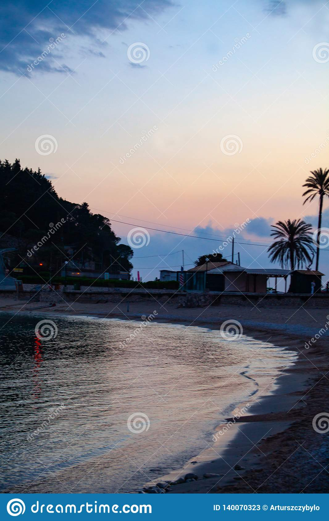 A sandy beach at the sea in the dusk with a blue sky in the background. Calm and peace concept on the holiday.