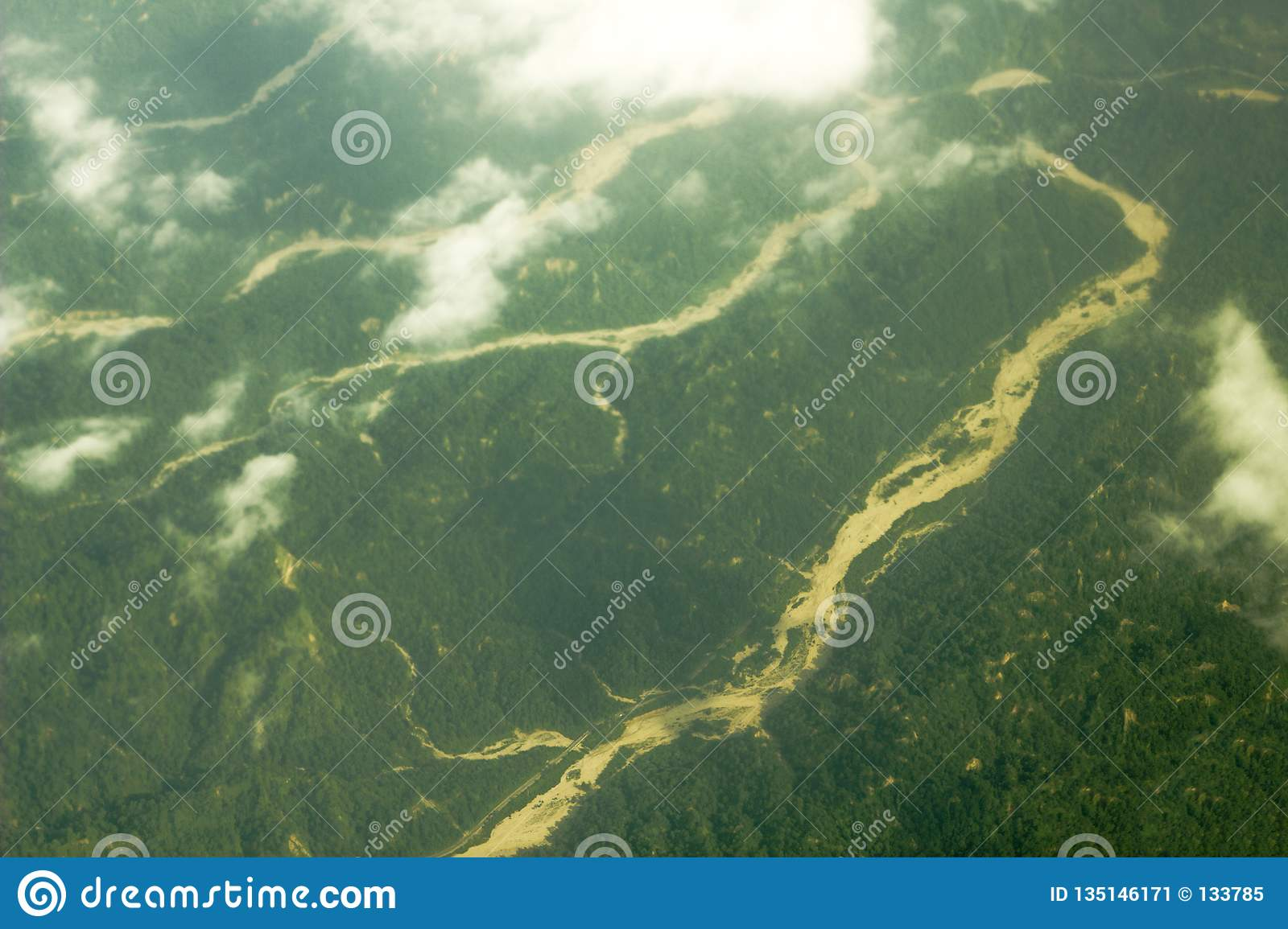 A sandy river bed among hilly green woodland. aerial photography white clouds over the valley