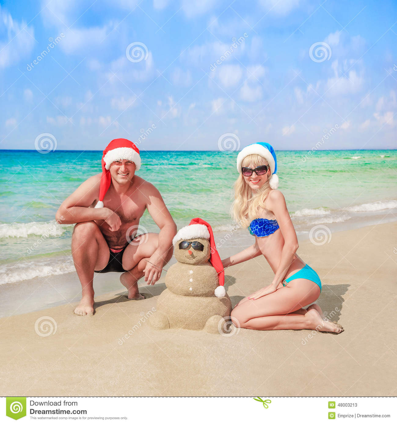 Sandy snowman in santa hat and young happy couple at beach stock sandy snowman in santa hat and young happy couple at beach kristyandbryce Gallery