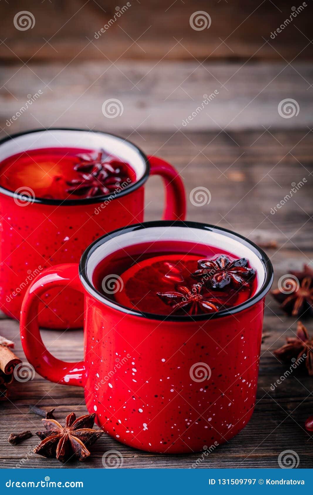 Sangria épicée de vin chaud de cidre d Apple de grenade dans des tasses rouges sur le fond en bois