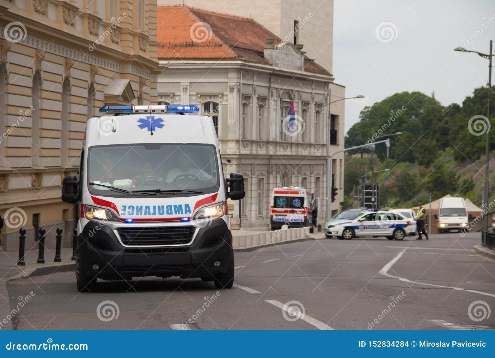 Sanitätswagen auf der Straße, mit Polizei im Hintergrund, allgemeines Ereignis sichernd