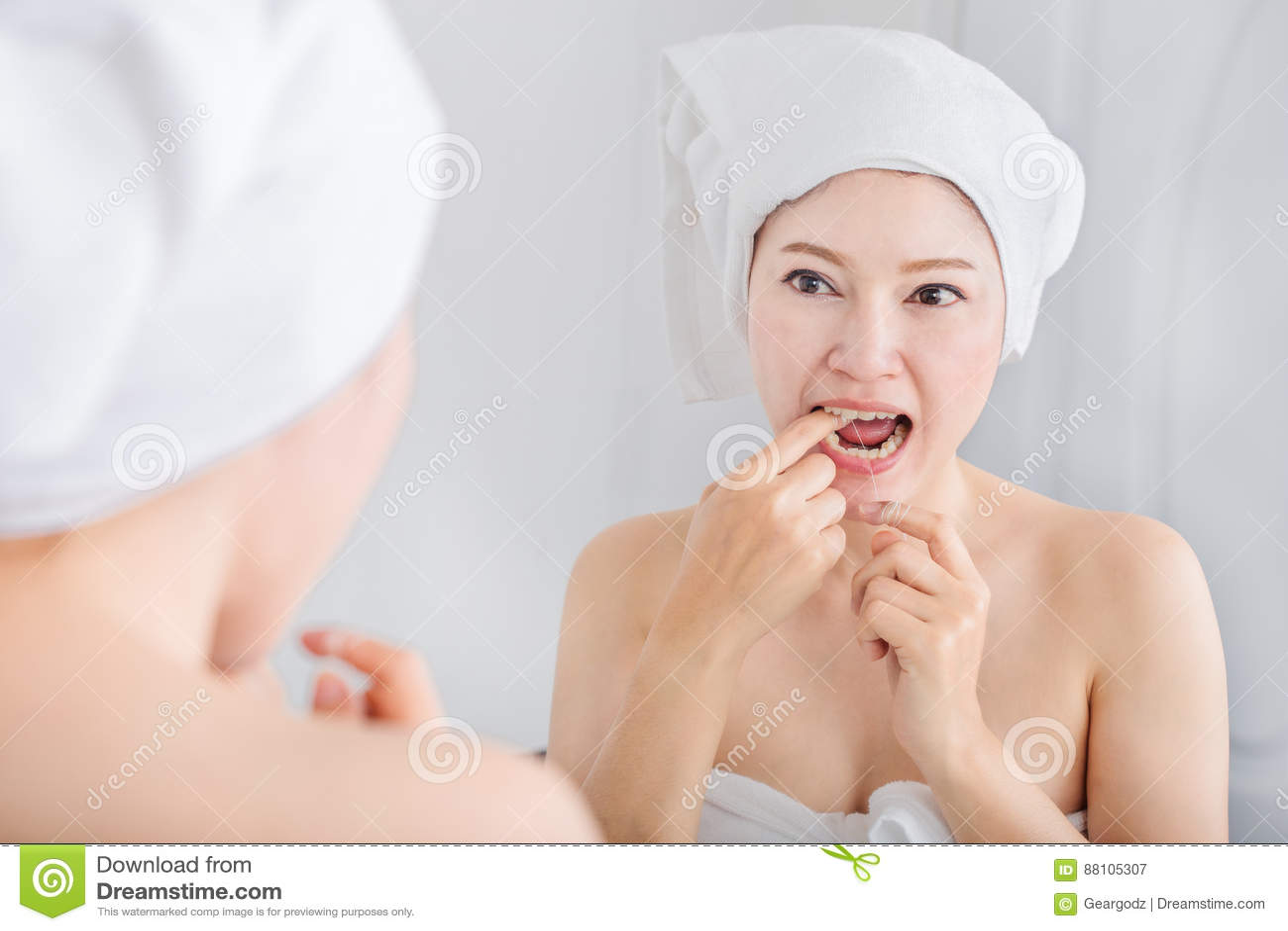 Sano blanco de la seda dental del uso de la mujer con el espejo en cuarto de baño