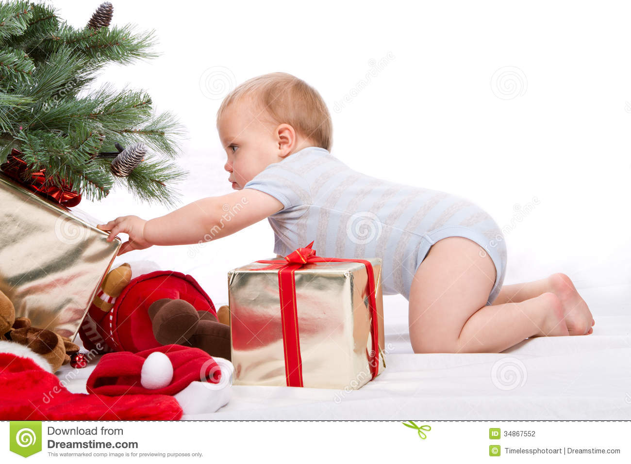 Baby Boy Gifts For Christmas : Santa baby boy reaching for christmas gift stock photo