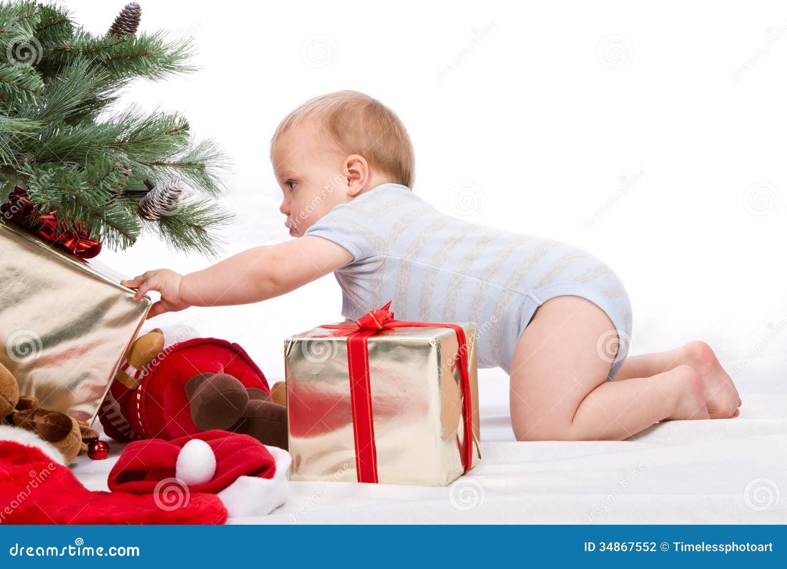 Santa Baby Boy Reaching For Christmas Gift. Stock Photo - Image of ...