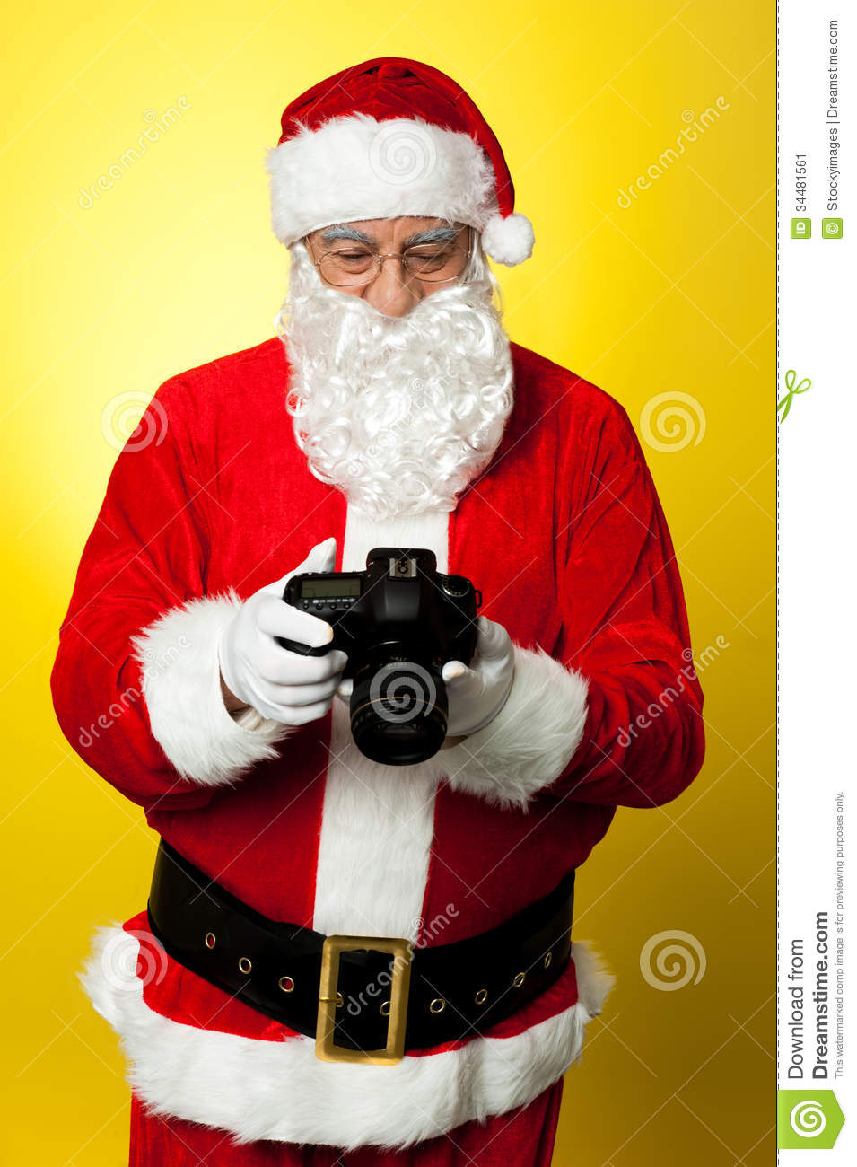 Santa Checking Pictures On His DSLR Camera Stock Image