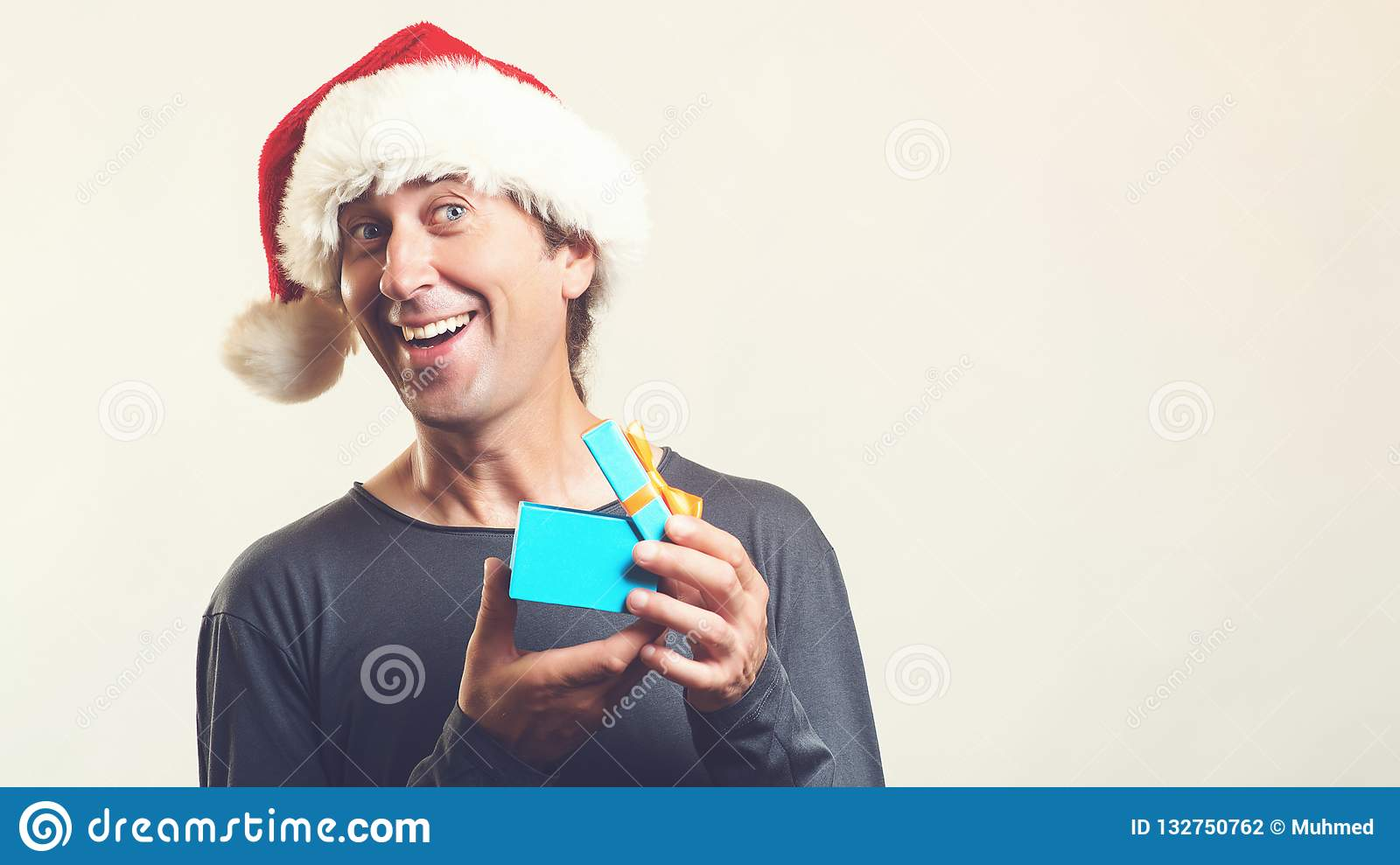 Santa christmas man opening gift box present. Amazing man in Santa hat isolated on white, with copy space. Christmas holidays.
