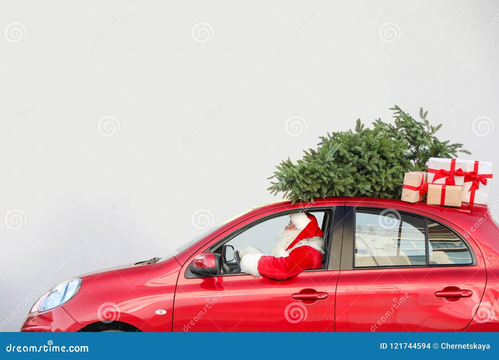 Santa Claus authentique conduisant la voiture rouge avec des boîte-cadeau