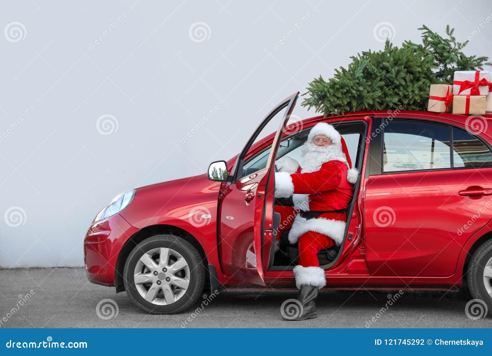 Santa Claus authentique dans la voiture avec les boîte-cadeau et l arbre de Noël
