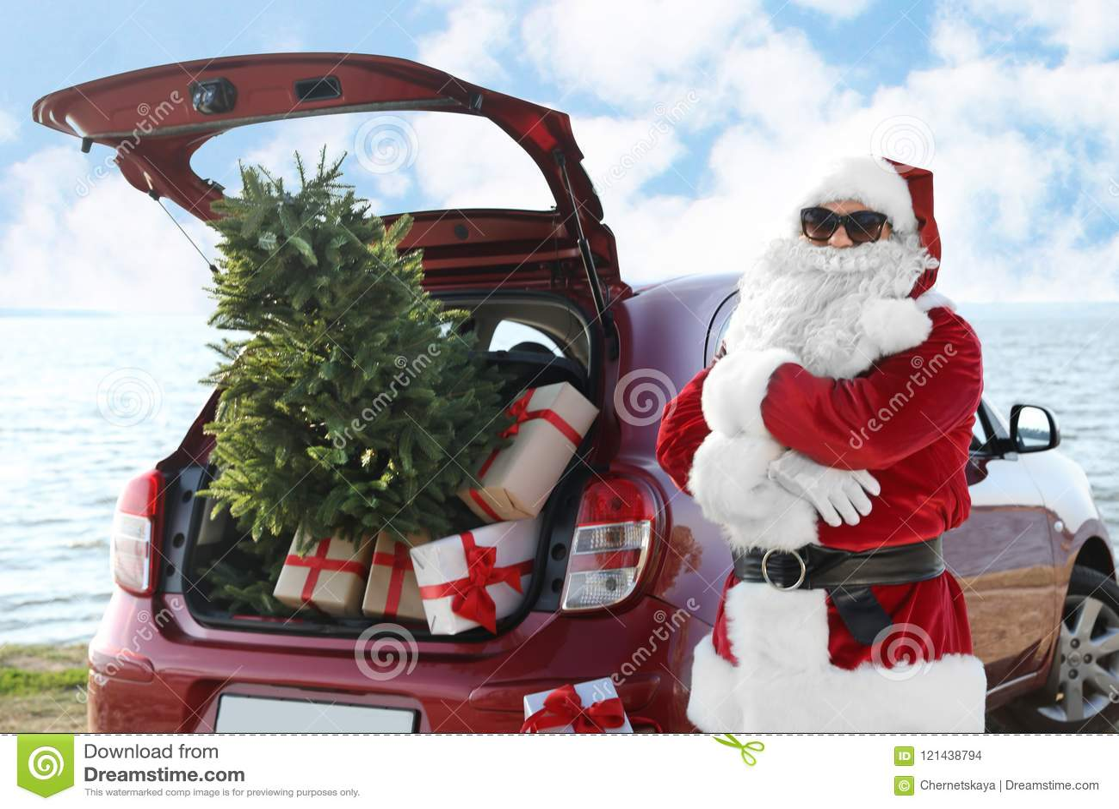Santa Claus authentique près de voiture rouge avec le cadeau et d arbre de Noël sur la plage