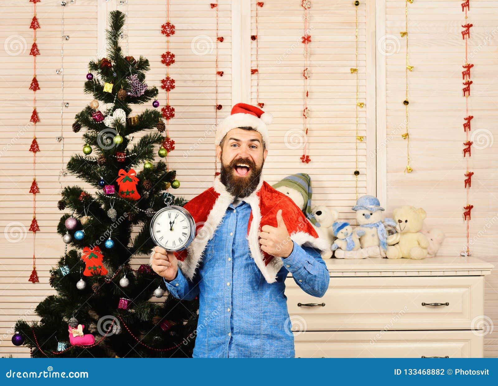 Santa Claus com a cara de sorriso perto da árvore e das festões de Natal