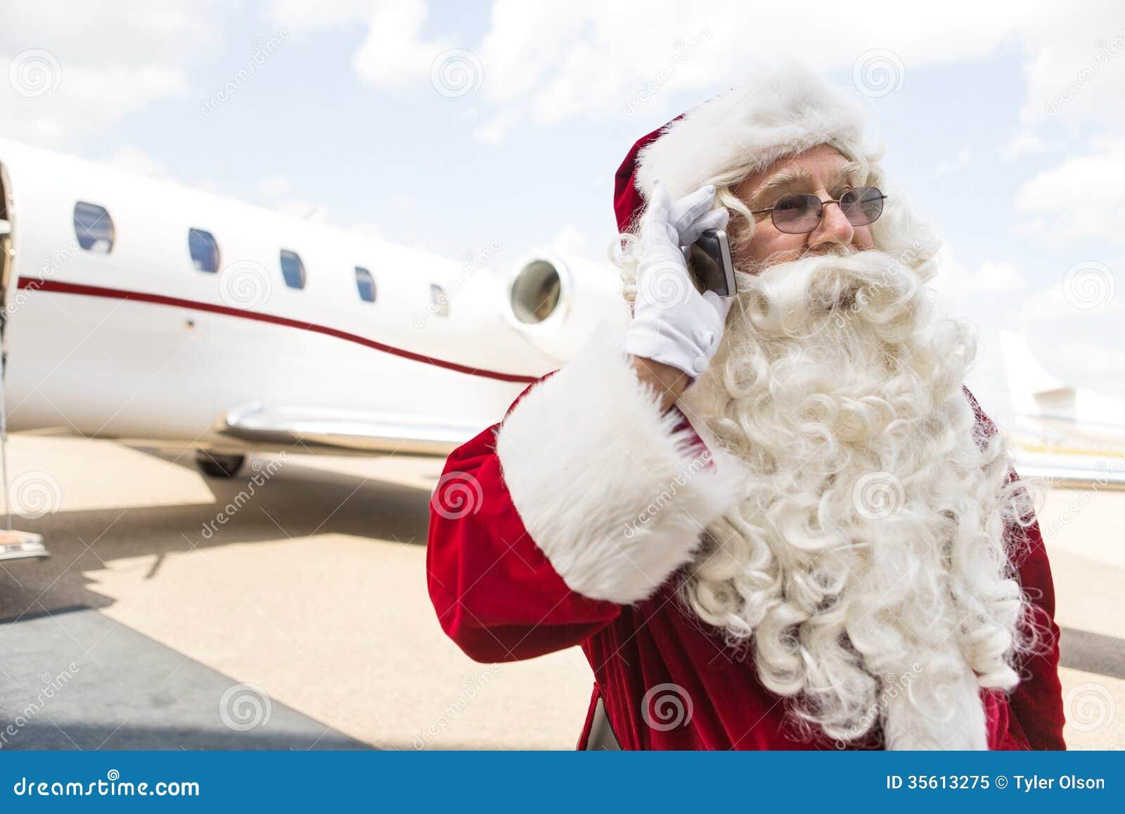 Santa Claus Communicating On Mobile Phone tegen