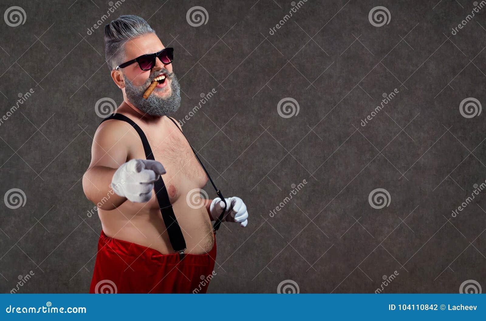 Santa Claus con un cigarro desnudo del vientre en sus dientes contra
