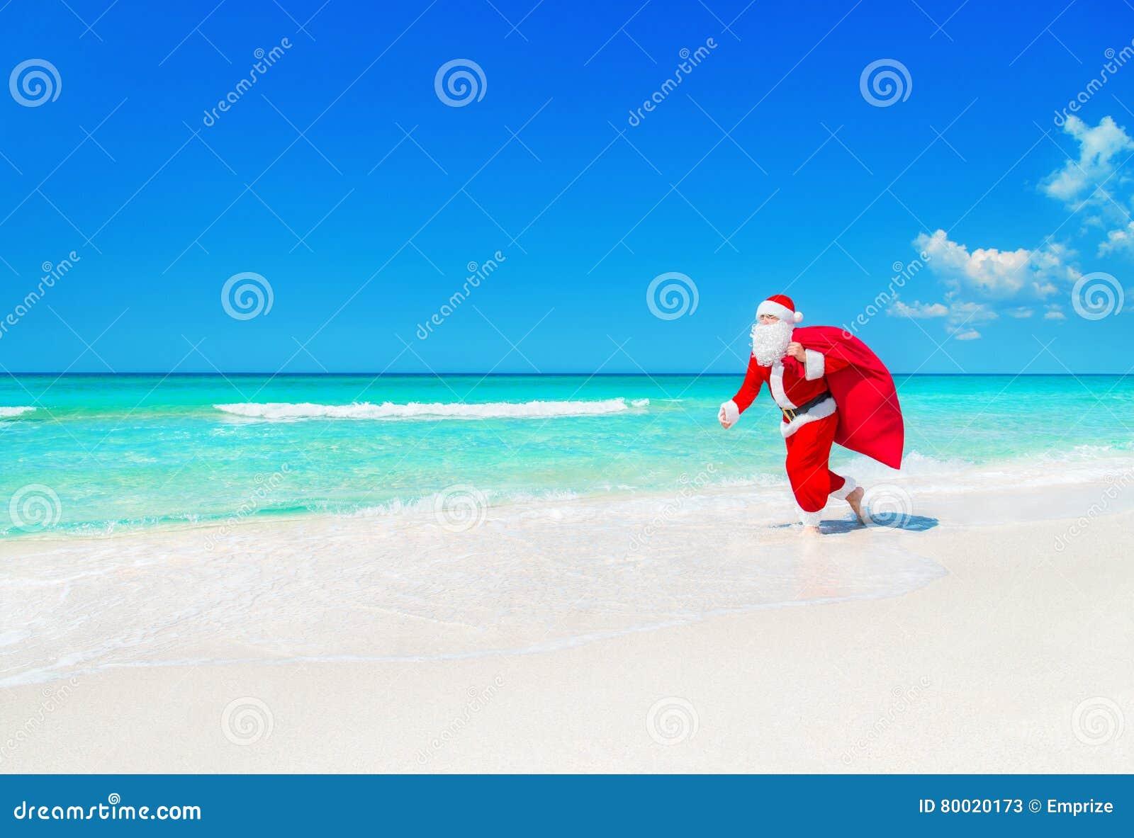 Santa Claus corre a lo largo de la playa del océano con el saco de los regalos de la Navidad