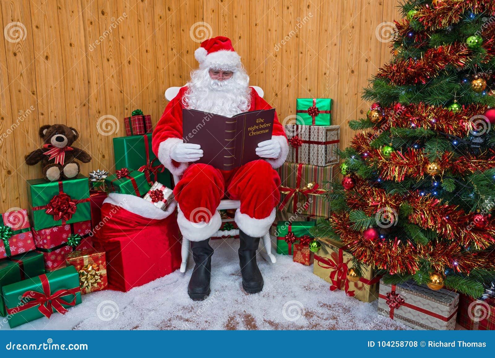 Santa Claus dans une grotte lisant son livre de Noël