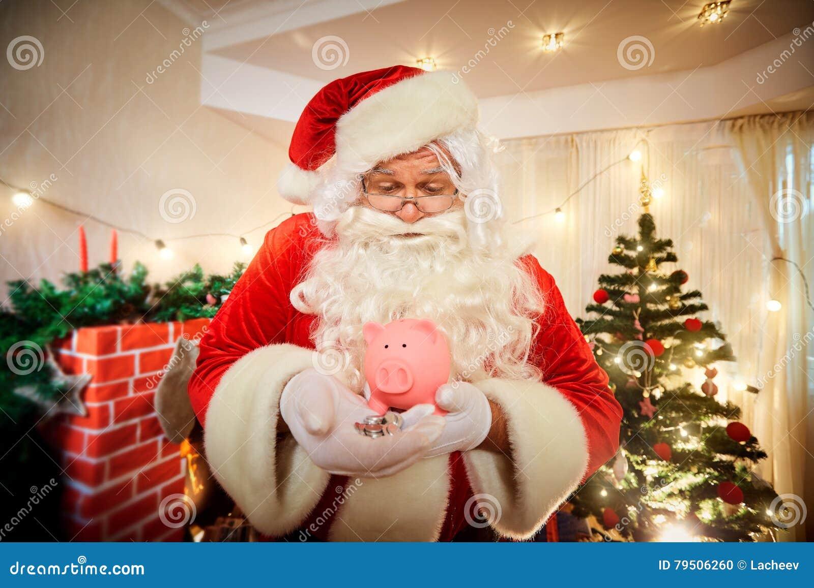 Santa Claus die een varkensspaarvarken en muntstukken in Kerstmis houden