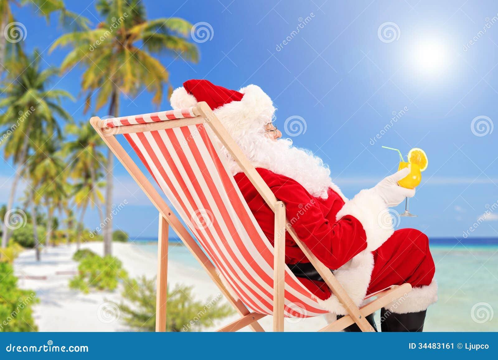 Santa Claus die op een stoel en het drinken een oranje cocktail liggen