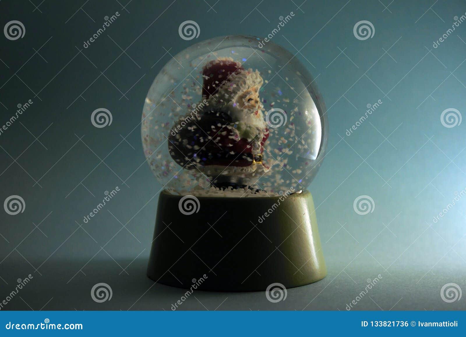 Santa Claus die zijn zak in een sneeuwstormbol dragen op blauwe achtergrond
