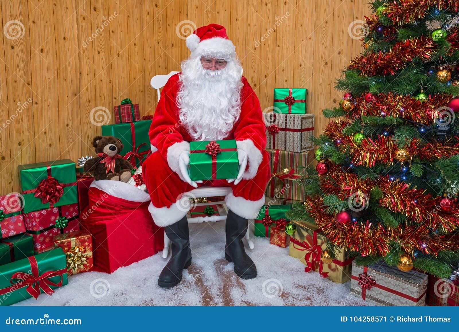Santa Claus in einer Grotte, die Ihnen ein Geschenk gibt