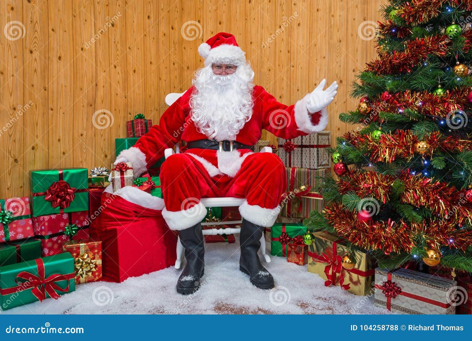 Santa Claus in einer Grotte Geschenke austeilend