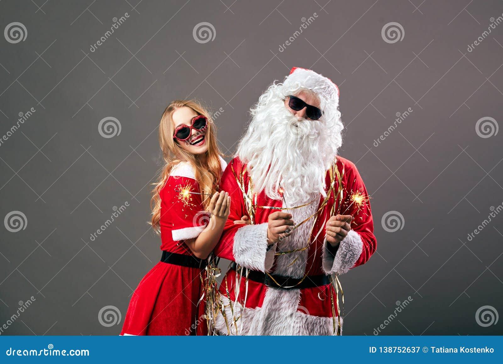 Santa Claus en jonge mooie Mevr. Claus in zonnebril houdt sterretjes in hun handen op de grijze achtergrond